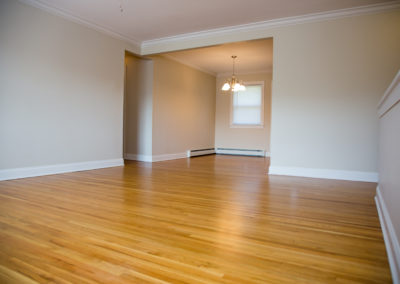Large, open living and dining space with beautiful hardwood floors and lighting at Jeanne Marie Gardens apartment