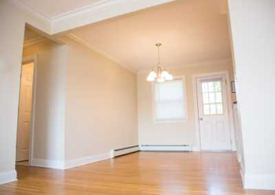 Entryway with new hardwood floors, crown molding, cream walls, and a white door with window