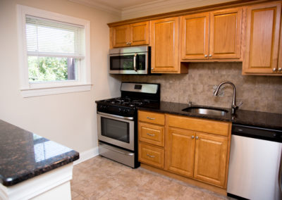Kitchen with large sink, stainless steel dishwasher, stove, and microwave, and small window