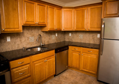 Beautiful, new apartment kitchen with large sink, bright wood cabinets, tile backsplash, and lots of outlets