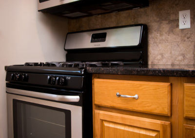 Oak cabinets next to stainless steel stove against tile backsplash in a Jeanne Marie Apartments' renovated kitchen