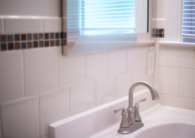Close-up of detailed bathroom tile behind silver faucet and white sink
