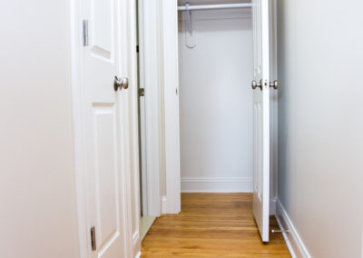 Hallway closets with white, modern doors and and clothes bar