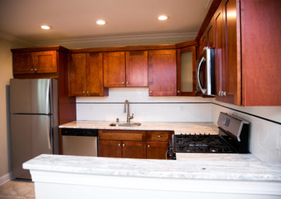 Beautiful, updated kitchen with cherry wood cabinets, white marble counters, and stainless steel appliances