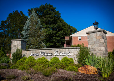 Jeanne Marie Gardens entrance with landscaping and stone welcome sign