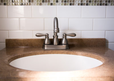 Brown countertop with silver faucet and white tile backsplash in apartment bathroom in Nanuet, NY