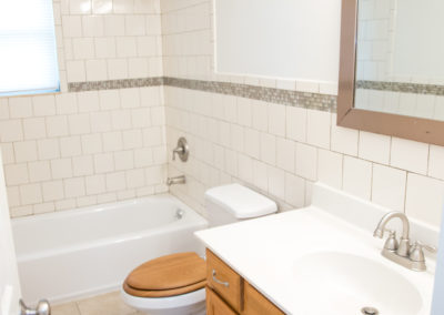 Tiled, large bathroom with white and wood toilet and vanity with sink