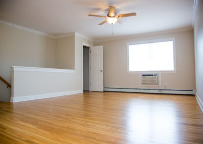 Large, open living space with new hardwood floors and ceiling fan at apartment for rent in Rockland County